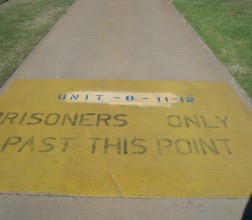 Image of path with painted text stating 'prisoners only past this point'.