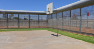 Photo of basketball court surrounded by security fence