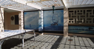 Photo of an outdoor exercise area, with a ping pong table and a large painting of a ship on the wall.