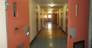 Image of a corridor with cells on either side at Acaica Prison