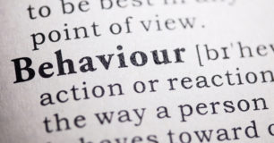 Close up image of the word Behaviour in a dictionary