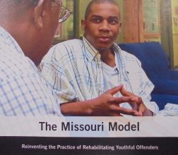 Image of two men talking, on front cover of report Missouri Model
