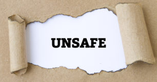 The word Unsafe shown through torn paper