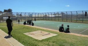 Image of prisoners sitting around the edge of a basketball court at Casuarina Prison.