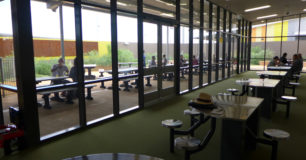 image of inside visits area, looking through the windows to the outside visits area also. Table and seating.