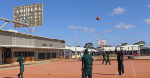 Image of prisoners on a basketball court, outside recreation