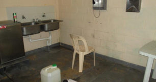 "Image of part of the ""recreation"" area with a double sink, and a plastic chair by a telephone on the wall, for the maximum security prisoners at Broome Regional Prison"