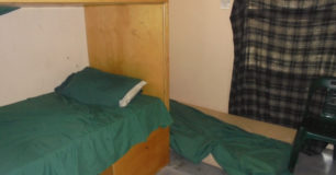 Image of double bunk beds, and a mattress on the floor by the window covered by a blanket at Broome Regional Prison