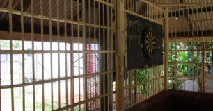 "Image of a dartboard attached to the bars of the ""bull-pen"" outside area used for recreation at Broome Regional Prison"