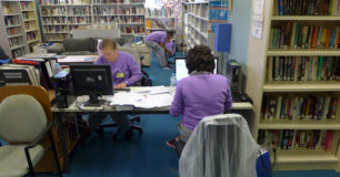 Women using computers in custodial library