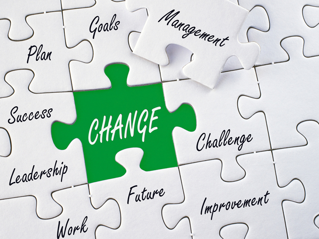 Image of a white jigzaw puzzle with words, and the word change in white with a green background