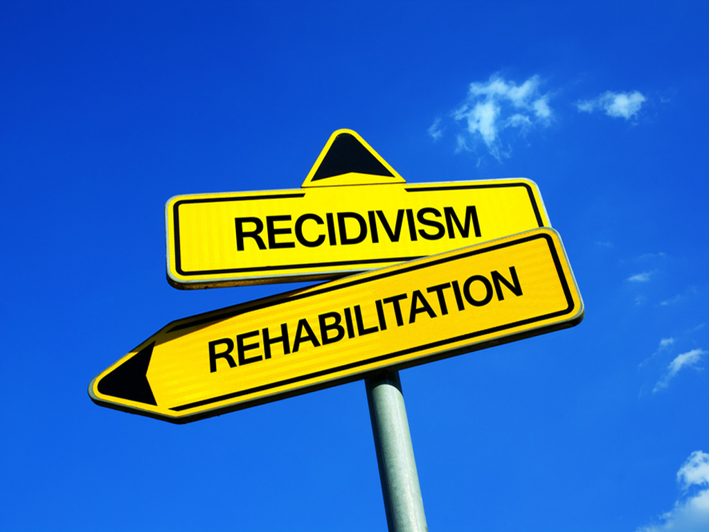 The words Recidivism and Rehabilitation on yellow arrow sign