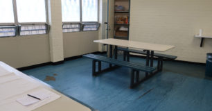 Image of a day room with tables and bench seats, in one of the units at Hakea