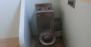 Image of an old style toilet and drinking water station in a court custody cell