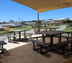Image of tables and benches in outside area at Acacia Prison