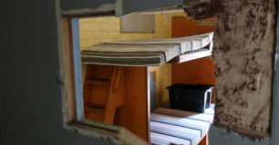 Image of looking through damaged Cell door into Cell in Unit 3