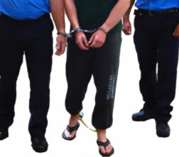 Image of a Prisoner handcuffed to a Prison Officer