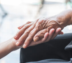 Older person's hand being held by carer
