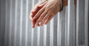 Prisoner handcuffed and behind bars